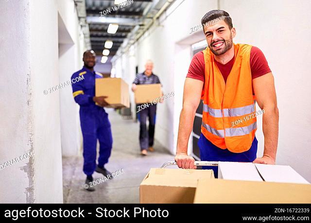 Lächelnder Arbeiter mit Warnweste schiebt Pakete auf Schubwagen ins Warenlager