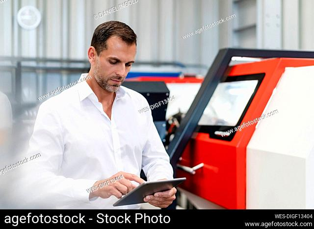 Businessman using digital tablet while standing by machinery at factory
