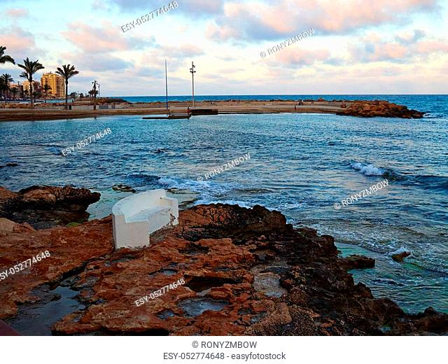 Bench made of stone in beautiful popular summer tourism destination Torrevieja beach, Costa Blanca, Valencia, Spain