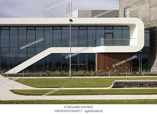 View of east facade and landscaped grass and seating. Menai Science Parc, Bangor, United Kingdom. Architect: FaulknerBrowns, 2019