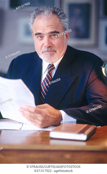 Mature executive businessman at desk