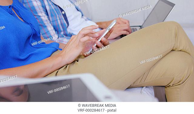 Couple using digital devices on sofa