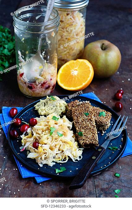 Orange, apple, and cranberry sauerkraut with spiced tofu coated in sesame seeds