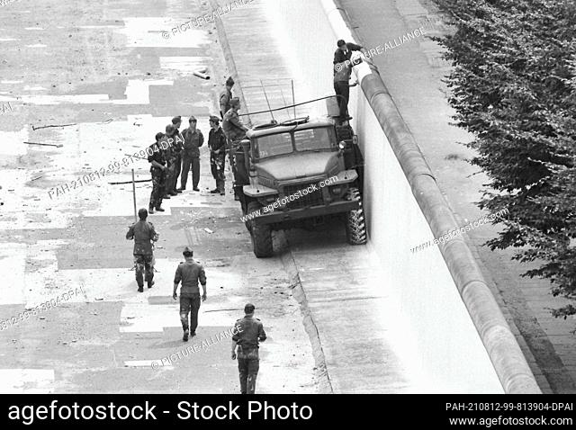 08 August 1985, Berlin: GDR border guards paint the Wall on Sebastianstraße in the Kreuzberg district with white paint. August 13