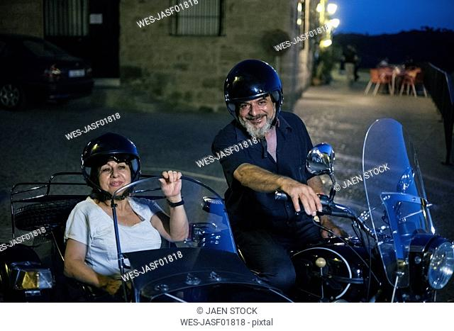 Spain, Banos de la Encina, portrait of mature couple on motorcycle with a sidecar at night