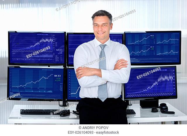 Portrait of confident stock market broker leaning on desk at office