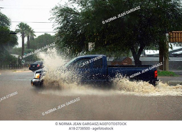 Trucks make their way through flooded streets during a monsoon storm, Sonoran Desert, Tucson, Arizona, USA