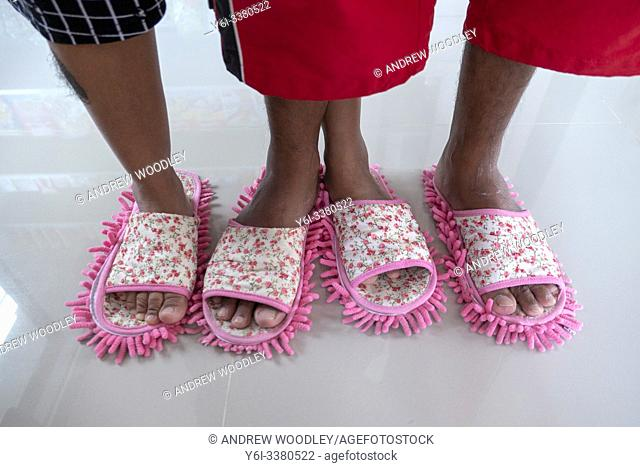 Store owners use floor cleaning slippers at beach shop. Ko Tao, Thailand
