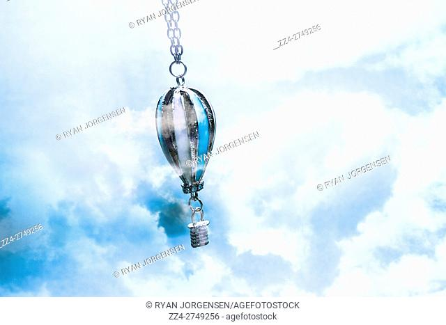 Close up of abstract air baloon hanging on metallic jewellery chain. Winds of mystery