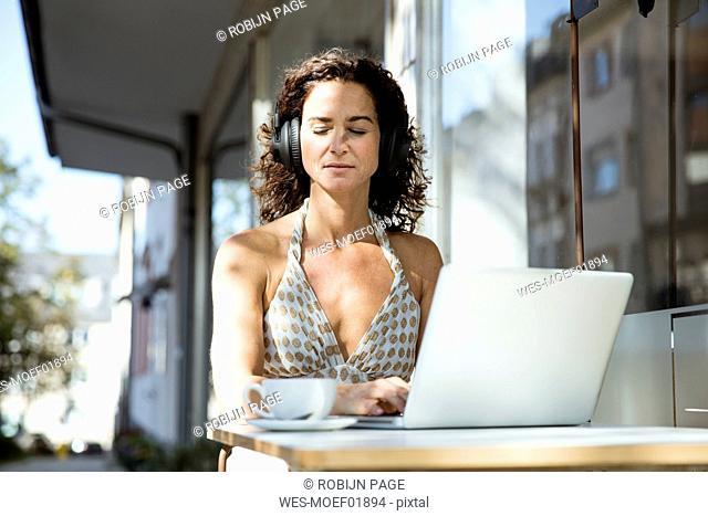Mature woman sitzting in cafe, wearing headphones, using laptop