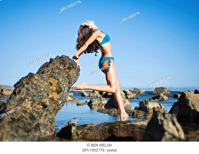 a young woman poses on the rocks on bunker beach, tarifa, cadiz, andalusia, spain