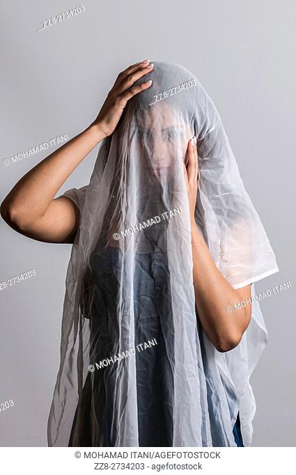 Woman covered with white chiffon fabric hands on head