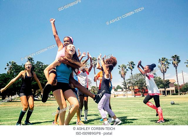Schoolgirl soccer team celebrating on school sports field