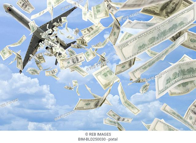Money falling in sky under airplane