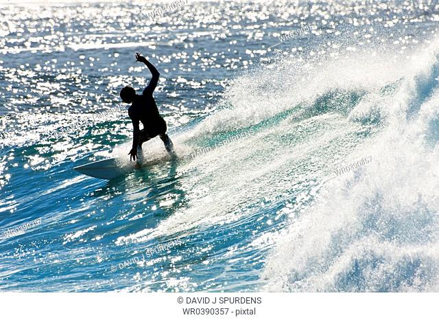 A surfer carving a sparkling wave
