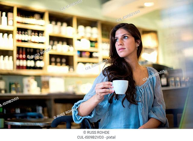 Young woman sitting in cafe looking sideways