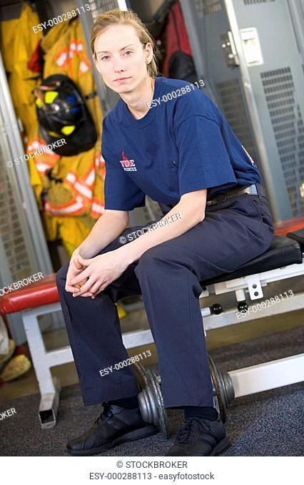 Firewoman sitting on bench in fire station locker room