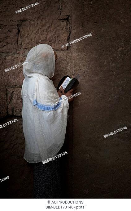Black woman reading at wall