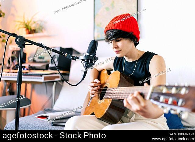 Female guitarist wearing knit hat while playing guitar at studio