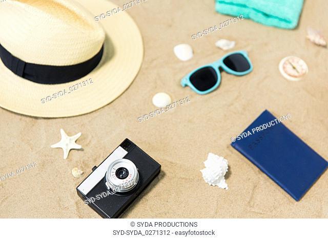 camera, passport, sunglasses and hat on beach sand