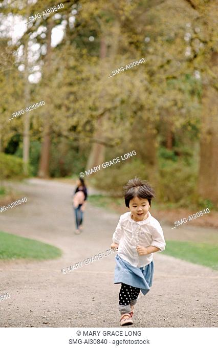 USA, Girl (2-3) running in park with mother in background