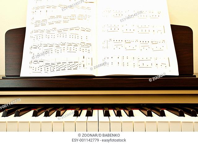Piano keys and music paper close-up