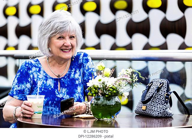 Mature woman checking her cell phone for messages while drinking an iced coffee at a cafe; St. Albert, Alberta, Canada