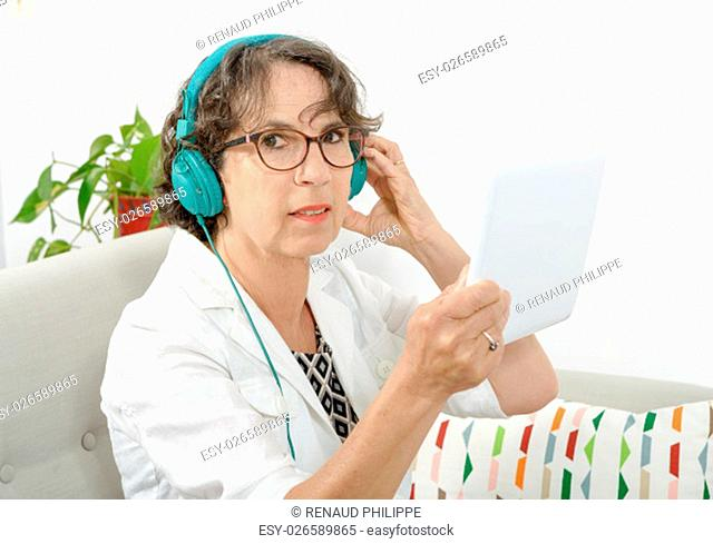 a beautiful mature woman listening to music with headphones