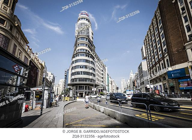 cars and people at Plaza de Callao subway station, Edificio Carrion Capitol building and Gran Via downtown Madrid, Spain