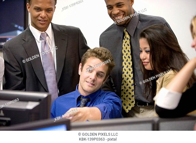 Close-up of office workers gathered around computer