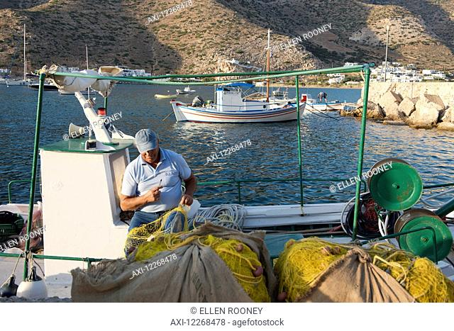A fisherman repairing his nets in the harbour; Kamares, Sifnos, Cyclades, Greek Islands, Greece