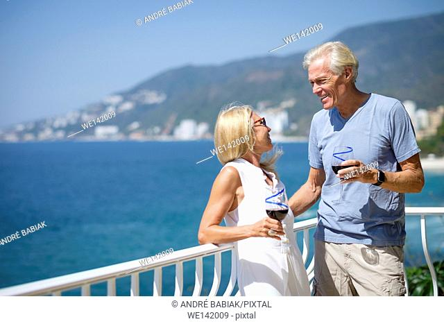 Senior man and woman enjoying red wine on the balcony of their ocean front house in Mexico