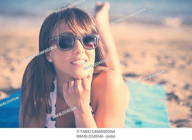 Caucasian woman laying on beach blanket