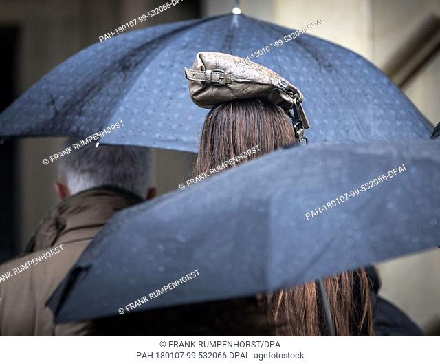 dpatop - A woman standing in a queue at the entrance to the Staedel Museum has placed a bag on her head to protect herself from the rain, in Frankfurt am Main