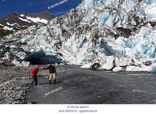 Couple crossing runoff water in front of Shoup Glacier, Shoup Bay State Marine Park, Prince William Sound, Valdez, Southcentral Alaska
