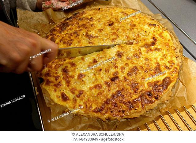 An freshly cooked onion cake is cut into pieces in Oberkirch, Germany, 13 October 2016. The savoury cake is mostly eaten in southern Germany