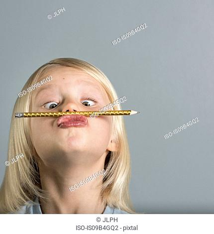 Portrait of boy balancing pencil on puckered lips