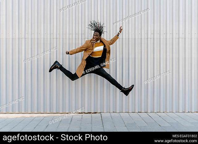 Man sticking out tongue while jumping against gray wall