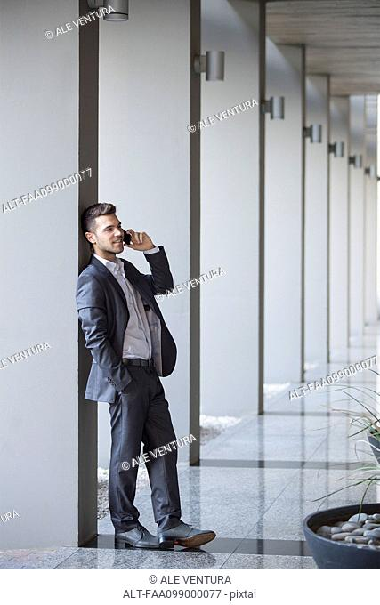Young executive taking phone call while leaning against column in building lobby