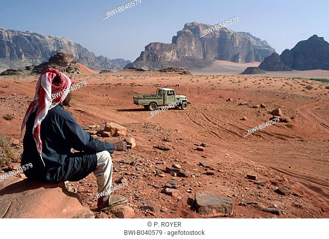 bedouin in the desert Wadi Rum, sitting on a rock, having a cigarette break, all-terrain vehicle close-by, Jordan