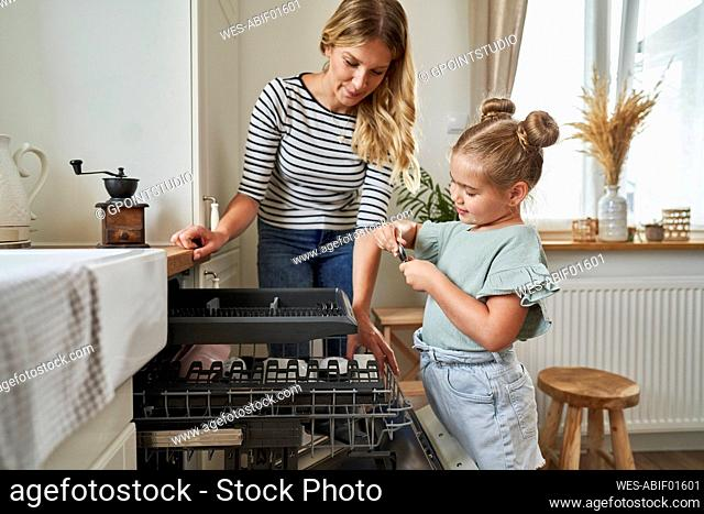 Woman and girl standing by dishwasher in kitchen
