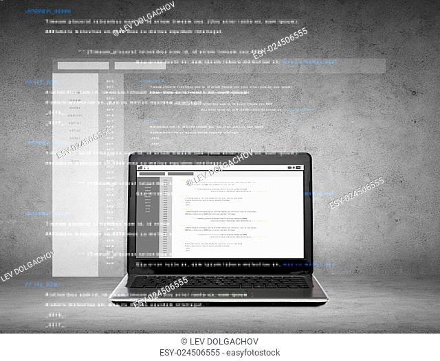 technology and programming concept - laptop computer with coding on screen over gray concrete background