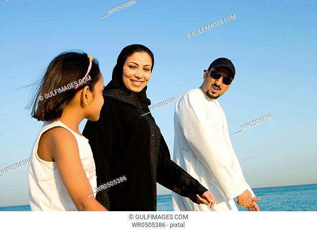 Girl with parents on beach, smiling, side view
