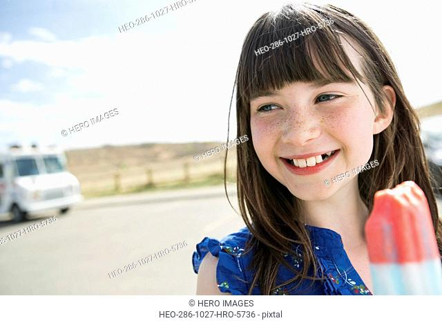 Smiling little girl holding ice lolly on road