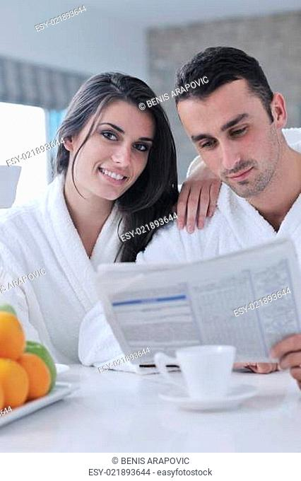 Happy couple reading the newspaper in the kitchen at breakfast