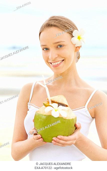 Woman drinking from a coconut