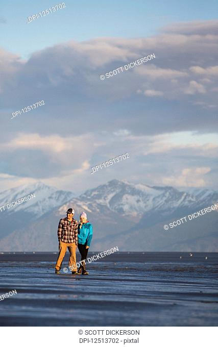 A young couple walking on a beach and holding hands with a mountain range in the distance; Anchorage, Alaska, United States of America