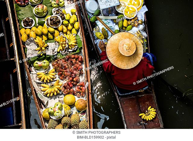 High angle view of merchant selling fruit in canoe
