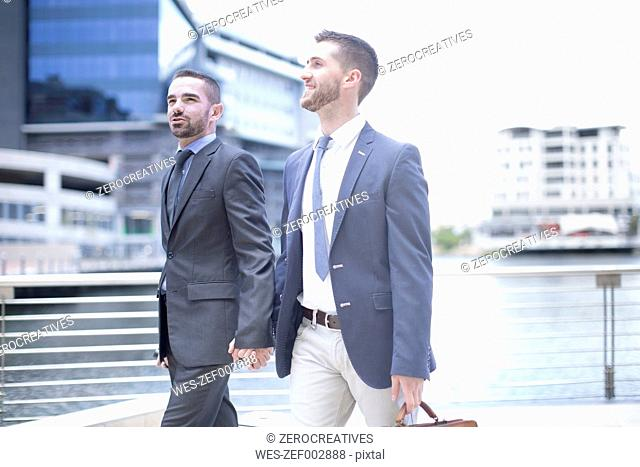 Gay couple walking with business suits