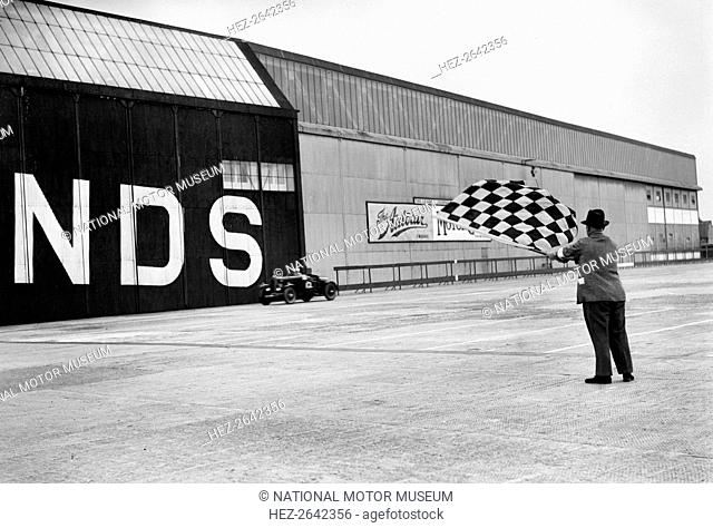 Waving the chequered flag at Brooklands, 1938 or 1939. Artist: Bill Brunell